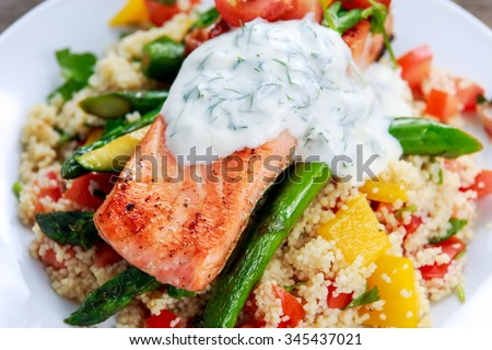 Pan fried Salmon with tender asparagus, courgette served on couscous mixed with sweet tomato, yellow pepper, greek yogurt with dill. - stock photo
