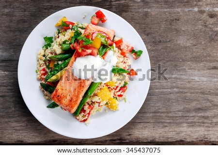 Pan fried Salmon with tender asparagus, courgette served on couscous mixed with sweet tomato, yellow pepper, with greek yogurt on old wooden table - stock photo