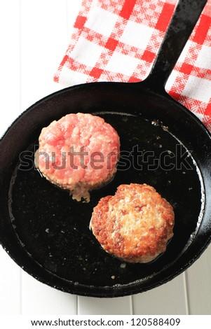 Pan frying burger patties - overhead - stock photo
