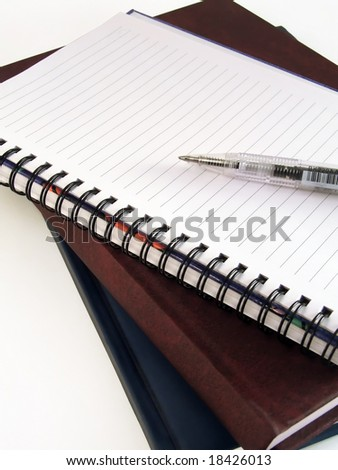 Pan laying on empty notebook and few books - stock photo