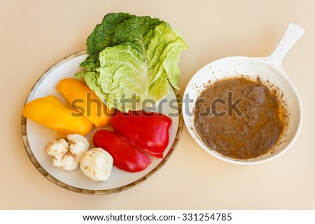 pan of bagna cauda with a plate of red and yellow peppers ,green cabbage and topinambour serving as trimming - stock photo