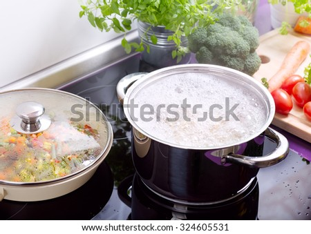 pan of boiling water with spaghetti on the cooker in the kitchen - stock photo