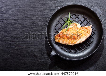 pan of grilled chicken breast on dark background - stock photo