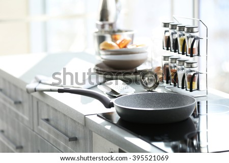 Pan on modern electric stove in the kitchen beside window - stock photo
