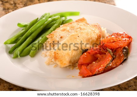 Pan Seared Tilapia on rice with tomatoes and green beans.