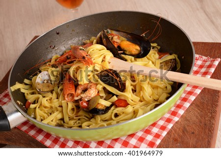 Pan with fettuccine pasta with fish and seafood side dish - stock photo