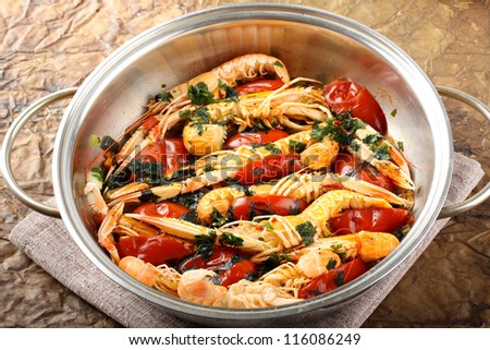 Pan with shrimp and tomatoes on complex background - stock photo