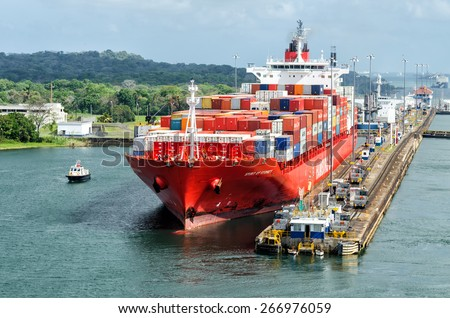 Panama Canal, Panama - February 20, 2015: Ship in Miraflores Locks Panama Canal, electric locomotives pull ships in transit through the locks  the Panama Canal  - stock photo
