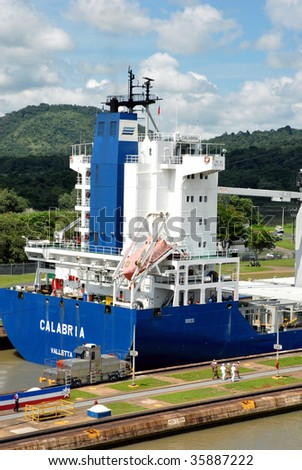 Panama Canal with a large container ship full of cargo in the background. - stock photo