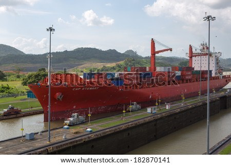 PANAMA CITY, PANAMA, JANUARY 3: Red Cap Stewart container ship entering in the basin of Miraflores Locks Panama Canal filling to raise a ship. Panama City, Panama 2014. - stock photo