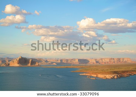 Panaromic view of Lake Powell with colorful orange and red rocks in late afternoon with scenic clouds in the sky - stock photo