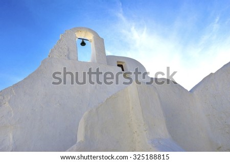 Panayia Paraportiani church in Mykonos island, Greece. A very typical, traditional, whitewashed christian greek orthodox chapel with dome in Little Venice in Chora against blue sunny sky. - stock photo