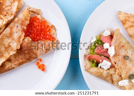Pancake day, mardi gras, maslenitsa background. Thin rolled pancakes, crepes with red caviar and salmon. Traditional Russian dish. - stock photo