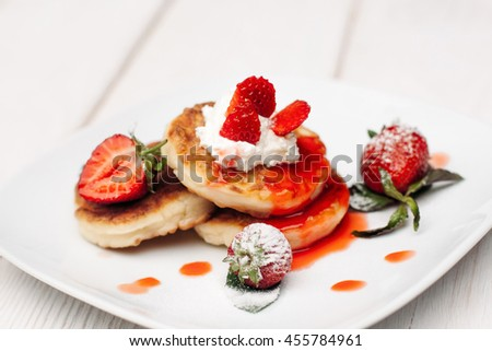 Pancake dessert with strawberries, cream and topping on white wooden table. Appetizing serving of sweet at restaurant - stock photo
