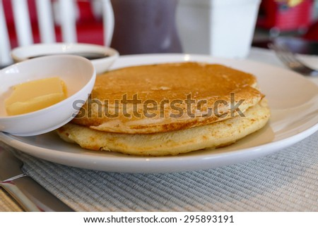 pancake serving with chocolate sauce and butter on white dish