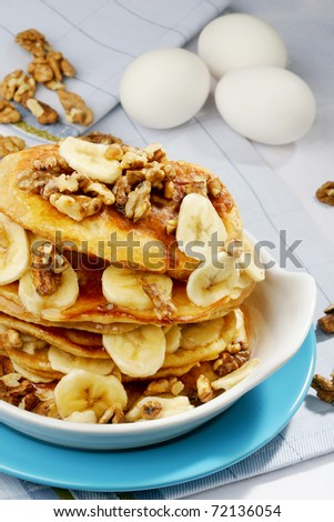 pancake stack with slices of banana and walnuts - stock photo