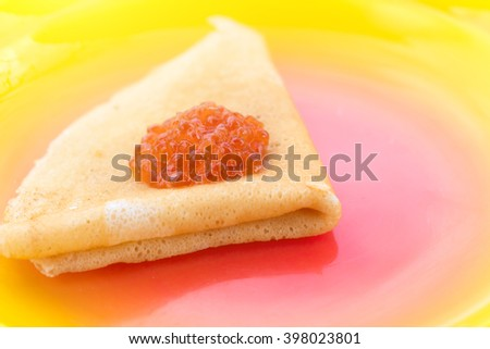 Pancake with red caviar on a yellow-red plate