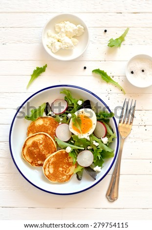 pancakes and egg salad on a light wooden surface - stock photo