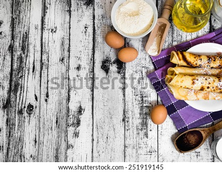 pancakes and ingredients on a wooden background - stock photo