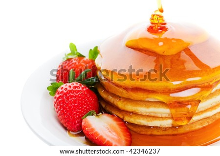 Pancakes and strawberry with heavy amount of maple syrup poured on top - stock photo