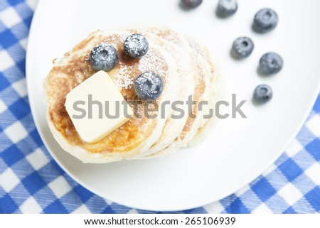 Pancakes, butter and blueberries on plate