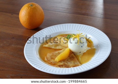 Pancakes crepes with ice cream scoop and orange sauce - stock photo