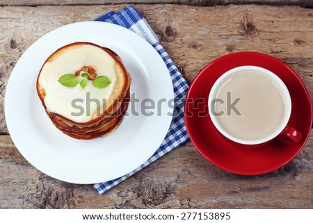 Pancakes for Breakfast.  Top view. Sweet food. Delicious Breakfast: pancakes and coffee. Coffee with milk and a stack of pancakes. Pancakes with condensed milk. Pancakes and vanilla sauce. - stock photo
