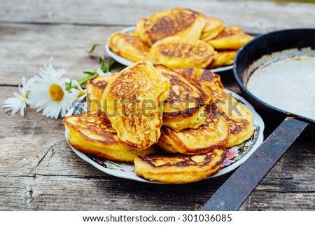 Pancakes on a plate next to the frying pan on a wooden table, DOF - stock photo