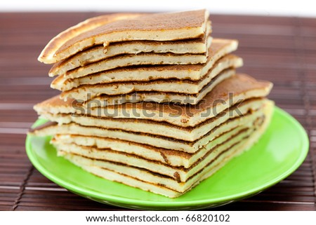 Pancakes on a plate on a bamboo mat