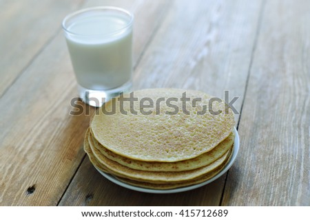 Pancakes on a white plate and milk in a glass, wooden background. Carnival.