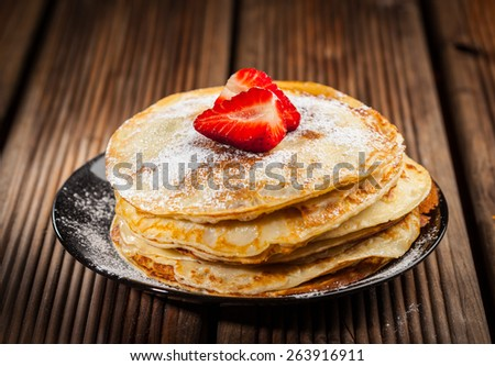 Pancakes or crepes with fresh strawberries and powdered sugar - stock photo