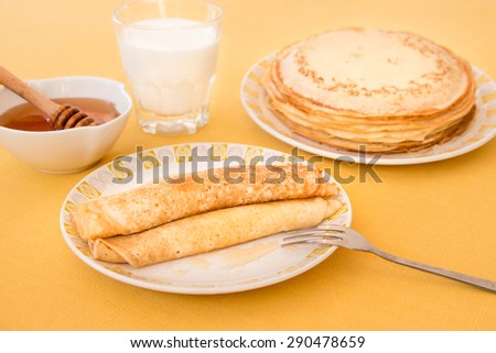 Pancakes rolled in a tube and poured honey on a plate, a glass of milk, a bowl of honey, a plate with a stack of pancakes. Pancakes and honey on the yellow tablecloth. Horizontal shot. Close-up.  - stock photo