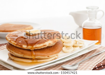Pancakes served with banana and topped with butter and maple syrup. - stock photo