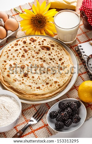 Pancakes served with milk and blackberry - stock photo