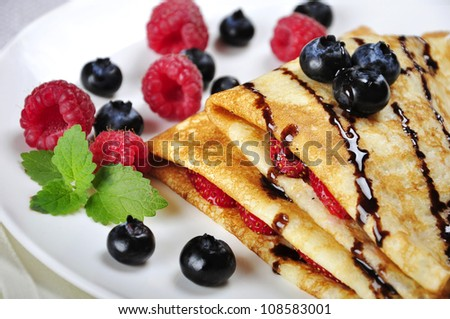 Pancakes served with raspberries, blueberries and chocolate on plate. Shallow dof - stock photo