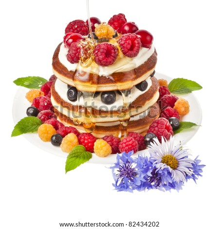 Pancakes stack with fresh berries and honey on white background - stock photo