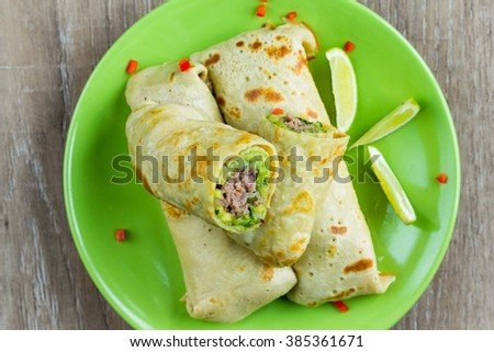 Pancakes stuffed with avocado sauce, meat beef kebab, Mexican tasty roll on shrove - stock photo