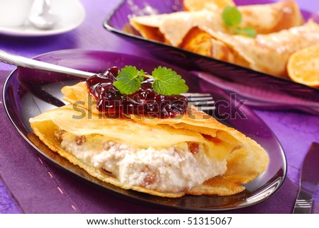 pancakes stuffed with cottage cheese and raisins poured blackcurrant confiture - stock photo