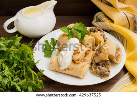 Pancakes stuffed with mushrooms and sour cream on a rustic wooden table - stock photo