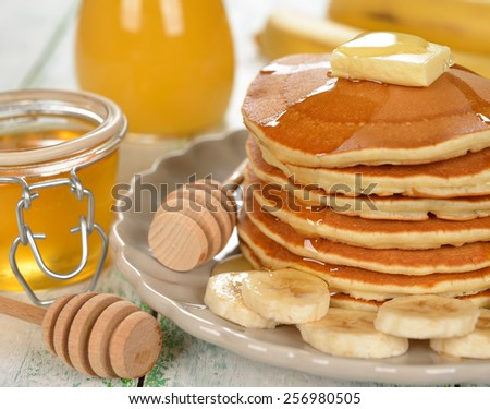 Pancakes with banana and honey on a white background - stock photo