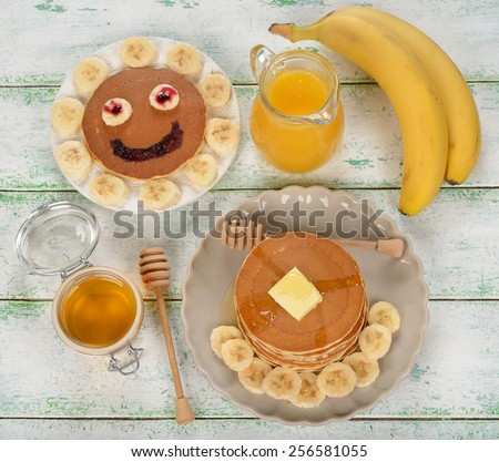 Pancakes with banana and honey on a white background, top view - stock photo