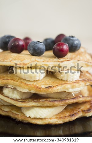 pancakes with banana, honey and blueberries for breakfast on a tray,