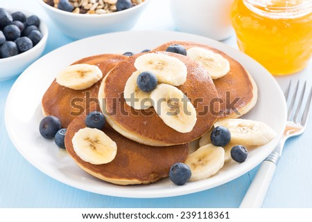 pancakes with banana, honey and blueberry on a plate, close-up - stock photo