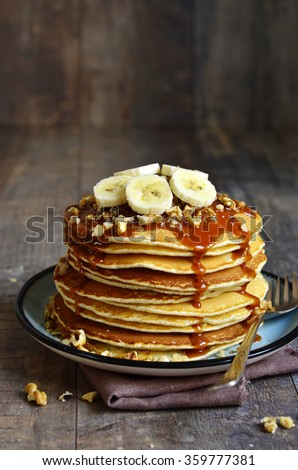 Pancakes with banana,walnut and caramel for a breakfast. - stock photo