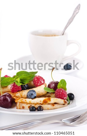 Pancakes with berries and mint and cup of coffee on a white background