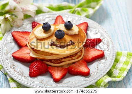 Pancakes with berries for kids - stock photo