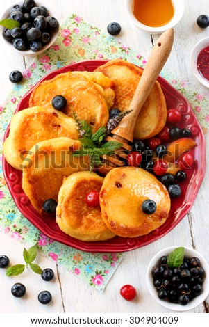 Pancakes with berries, fruit and honey - stock photo