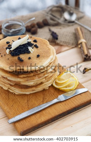 Pancakes with black caviar and butter on wooden table closeup macro - stock photo
