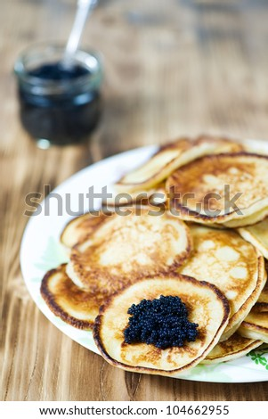 Pancakes with black caviar on the plate - stock photo