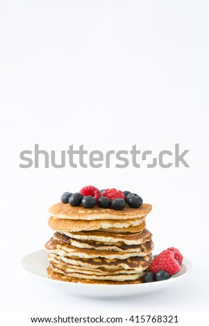 Pancakes with blueberries and raspberries isolated on white background
